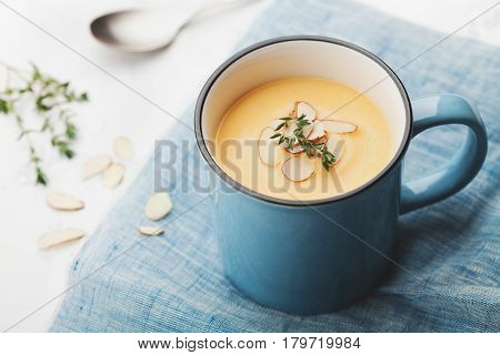 Dietary vegetable cream soup from carrot and potato decorated almonds flakes in blue cup on rustic background.