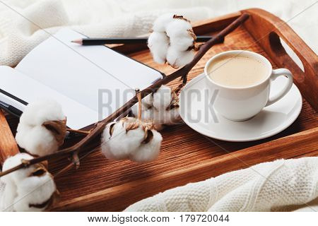 Cozy breakfast with cup of coffee, cotton, flower, macaroons and open notebook on rustic wooden tray in bed.