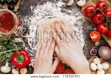 Woman Preparing Dough For Pizza. Hands Kneading Dough On The Wooden Table, Top View