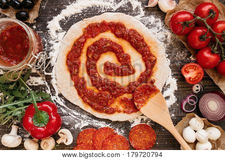 Cooking Pizza. Adding Fresh Tomato Sauce To Pizza Dough. Pizza Ingredients On The Wooden Table Top V