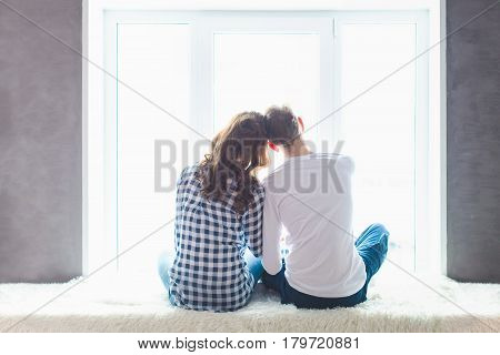 Back view of happy beautiful couple embracing and looking out the window.