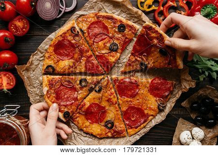 Eating Pizza, Top View. Hands Taking Slices Of Hot Delisious Pizza. Pizza Ingredients On The Wooden