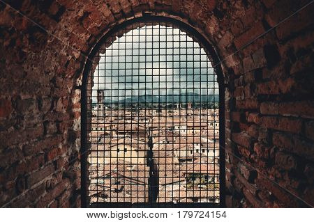 Medieval Town Lucca viewed through vintage window with historic buildings in Italy.