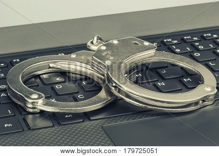 Handcuffs On The Laptop With Green Toning. Hacker Cyber Crime Concept.