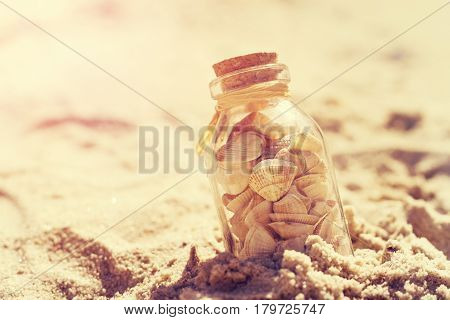 Summer or vacation concept. Seashells in bottles on sand. Toning.