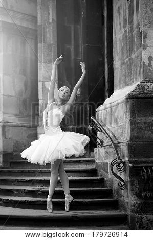 Balance is crucial. Monochrome soft focus shot of a young ballerina performing on the stairs of an old house
