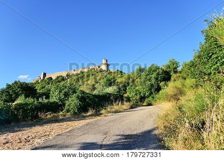 Cracked paved road and medieval Assisi fort panorama. Rocca Maggiore citadel of Assisi and the valley of Tescio Assisi Umbria Region Perugia Metropolitan Italy.