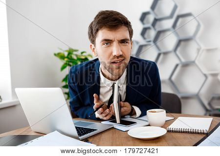 Displeased young businessman in sitting at workplace, looking at camera, office background.