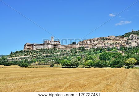 Panoramic view of the historic town of Assisi and Basilica of St. Francis with sloping field in front. Valley of Tescio Assisi Umbria Region Perugia Metropolitan Italy.