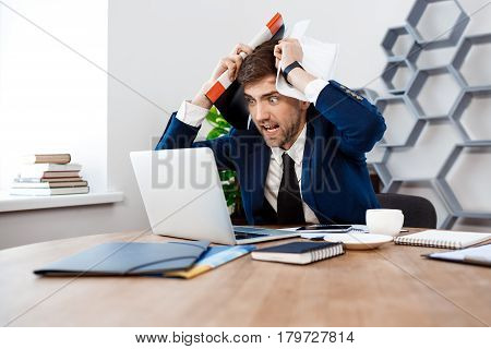 Angry young businessman in suit sitting at workplace, looking at laptop, holding papers, hands on head, office background.