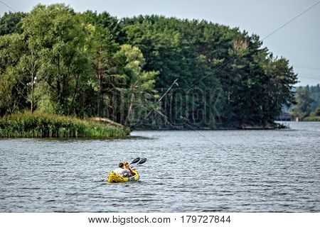 Couple kayaking on yellow inflated kayak on the lake or river with green forest on the bank