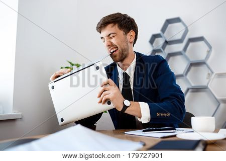 Angry young businessman in suit sitting at workplace, gnawing laptop, office background.