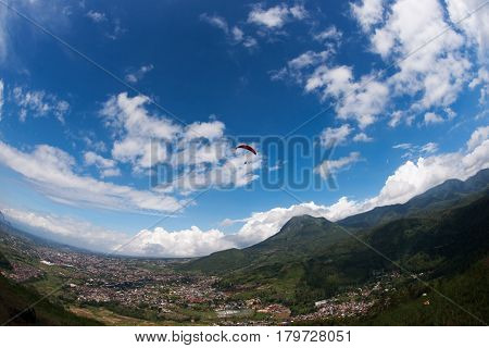One paraglider in the blue sky with red parachute gliding for fun and excitement towards the mountains villages and fields on the ground.