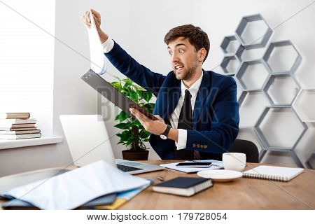 Angry young businessman in suit sitting at workplace, looking at folder with papers, office background.