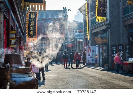 Tianjin, China - Nov 1, 2016: Tianjin Ancient Cultural Street, preserved in the classical Qing Dynasty architectural style. Steam emanating from an urn. Morning scene to what is a very popular tourist area.