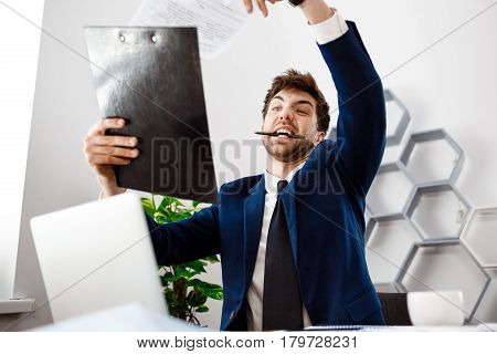 Angry young businessman in suit sitting at workplace, looking at folder with papers, gnawing pen,  office background.