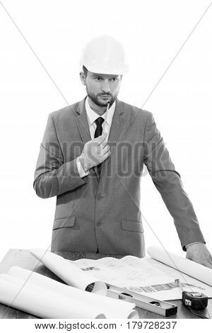 Thinking hard. Monochrome shot of a handsome bearded mature male businessman engineer in a hardhat looking away thinking while drawing up a building plan professionalism occupation career concept