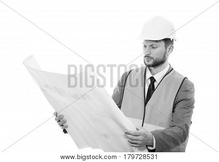 Working concentration. Black and white shot of a serious male constructionist in a hardhat and safety vest looking at the blueprints on white background professionalism success development concept poster