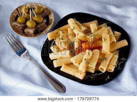 Black plate of pasta with sauce and watercress. Canape with pate and olives