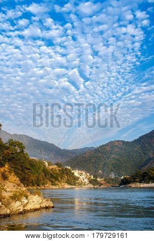 View of River Ganga and amazing blue sky with little clouds at beautiful colorful day with a colorful jungles on a background and colorful houses. Rishikesh. India.