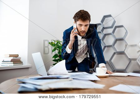 Absentminded young businessman in suit speaking on phone at workplace, office background.