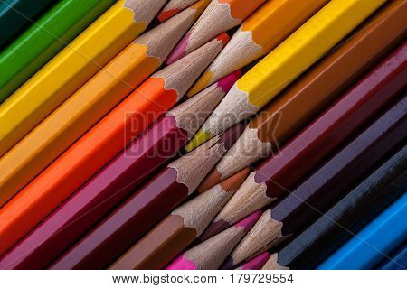 Top view of multicolored sharpened pencils. Colorful wooden crayons background. School, drawing and sketching supplies.