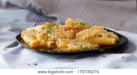 Black plate of pasta with sauce and watercress