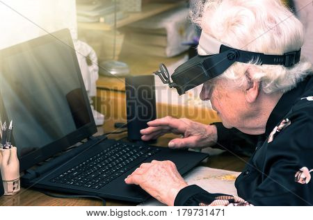 grandmother learns to work at home on the computer and internet In big special glasses virual reality