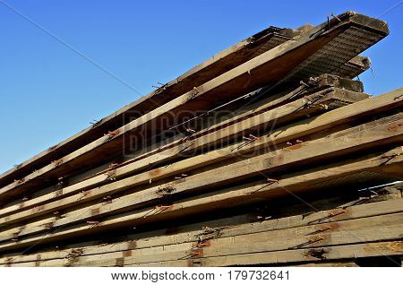 Rust coated nails stick out of reclaimed dimension wood boards used for rafters