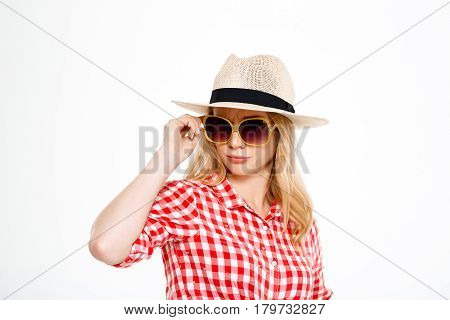 Portrait of young beautiful country girl in hat and sunglasses looking at camera over white background.