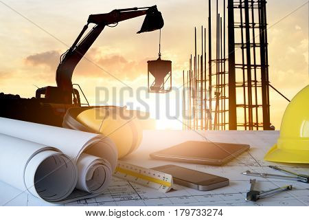 Desk of civil engineer with background silhouette of excavator activity machine