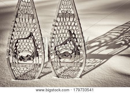 vintage wooden Huron snowshoes with leather binding in snow with shadow, retro sepia toning