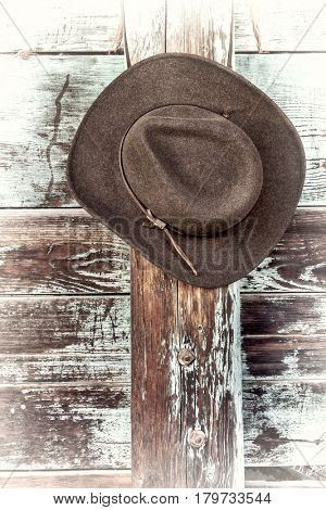 brown wool felt cowboy hat with leather headband hanging on weathered wooden corral fence, retro hand tinted processing