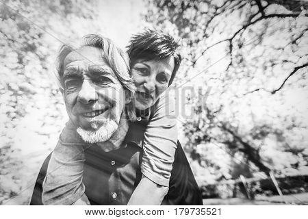 Senior couple piggyback riding in a park, Tuebingen, Germany