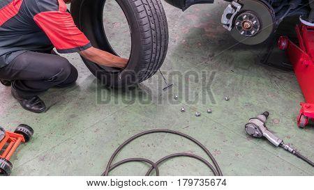 A car mechanic fixing a flat tire in Auto Repair Shop