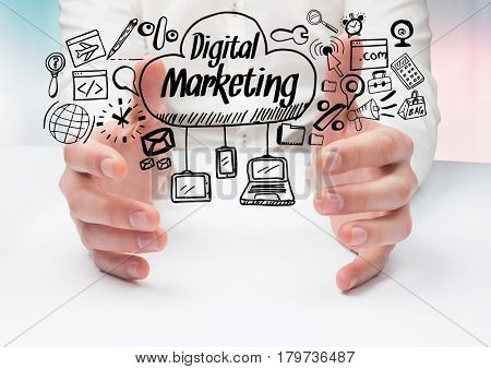 Digital composite of Hands on table and black digital marketing doodles against blue pink background