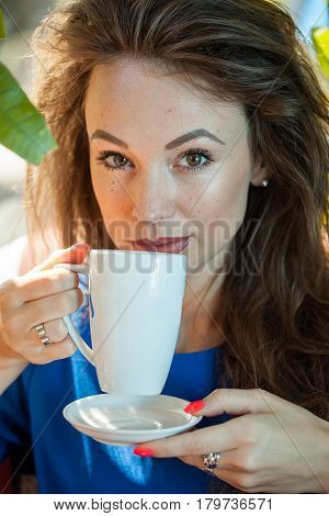 Beautiful young woman holding a cup of coffee. Coffee drinker.