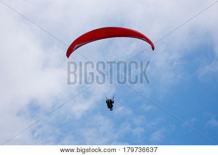 One paraglider in the blue sky with red parachute gliding for fun and excitement towards the ground.