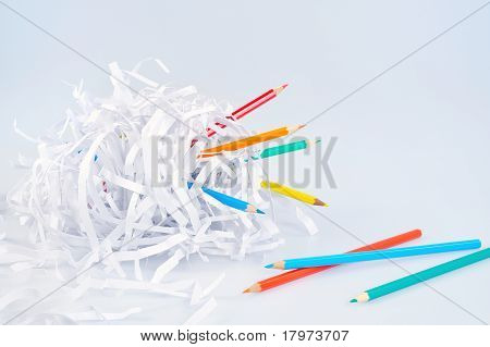 Colored pencils and shredded paper ball over light blue background with soft shadow