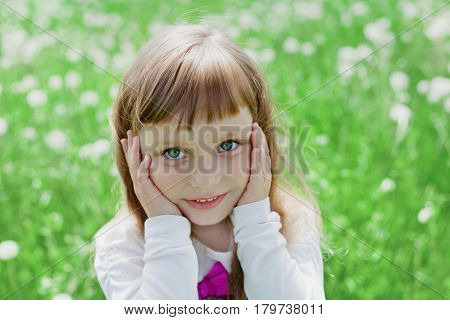 Closeup emotional portrait of cute little girl with beautiful soulful eyes standing on a green meadow. Happy childhood.