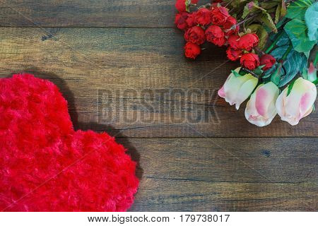 Heart shaped pillow and roses on wooden background Valentine's day concept