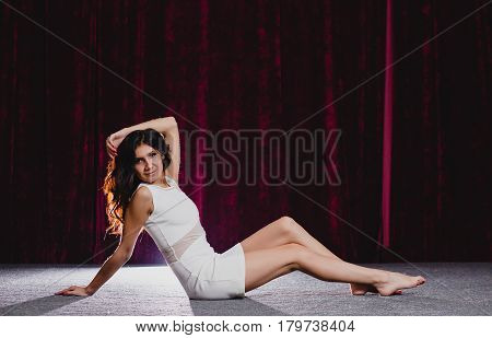 Young slender brunette in white dress lying on the floor