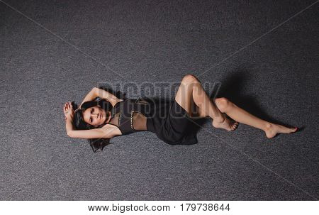 Young slender brunette in black dress lying on the floor