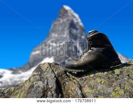 Hiking shoe on the rock, in the background mount Matterhorn - Pennine Alps, Switzerland