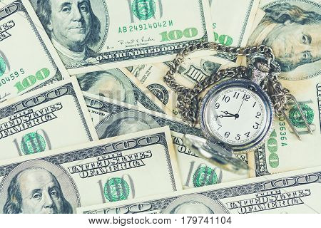 Time is money concept : pocket watch placed on U.S dollar bills