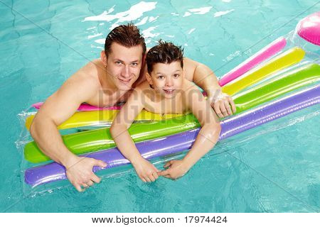 Photo of happy lad and his father in water