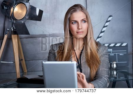 Portrait of thoughtful young businesswoman sitting in studio with tablet, looking away.