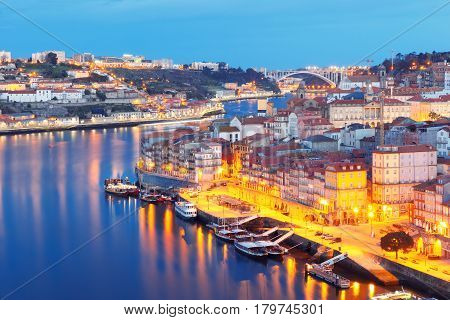 Picturesque aerial view of Old town of Porto, Ribeira and bridge with mirror reflections in the Douro River during morning blue hour, Portugal