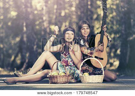 Two happy young girls with fruit baskets in summer forest. Stylish fashion female model outdoor