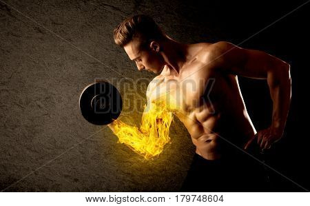 Muscular bodybuilder lifting weight with flaming biceps concept on background